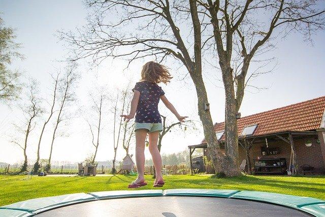 פעילות גופנית לילדים בחצר הבית עם טרמפולינה
